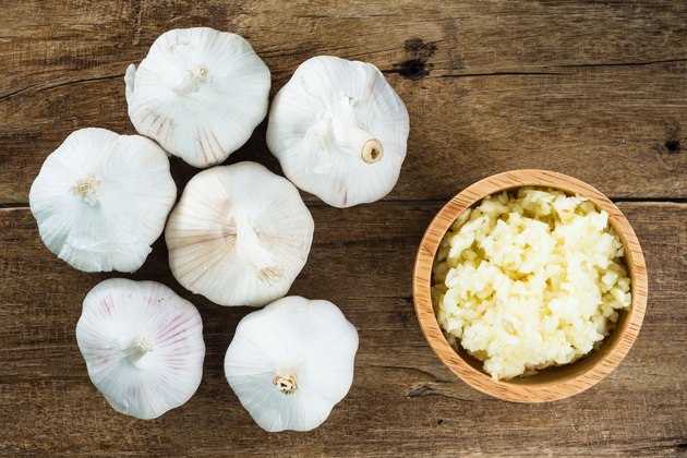 mased white garlic in wooden bowl with garlic cloves on wood table, top view