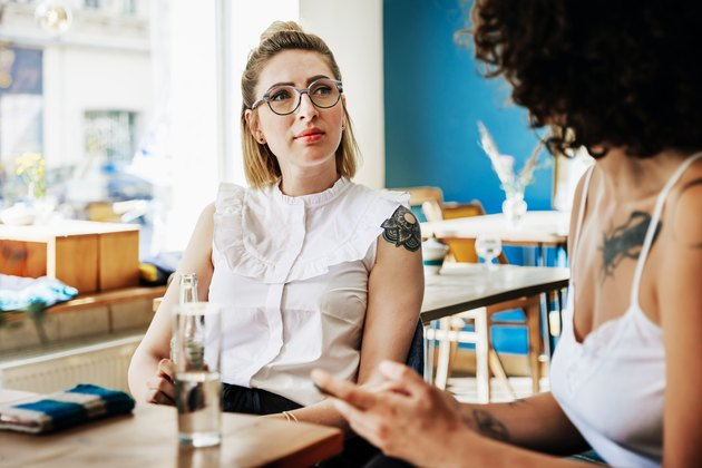 Two Stylish Young Women Having Conversation Together In Cafe