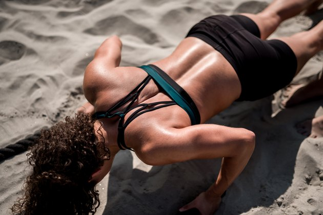 Women athlete doing workout on the beach