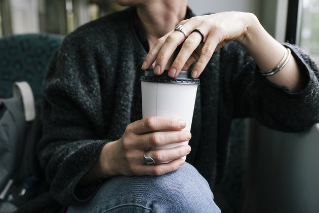 A woman holding a cup of healthy coffee
