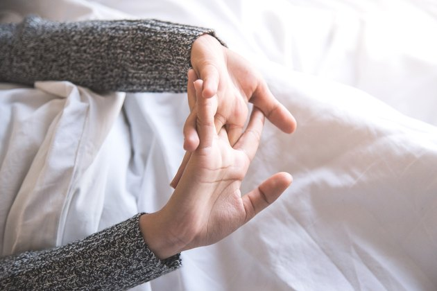 Cropped Image Of Woman Stretching Hands While Lying On Bed At Home