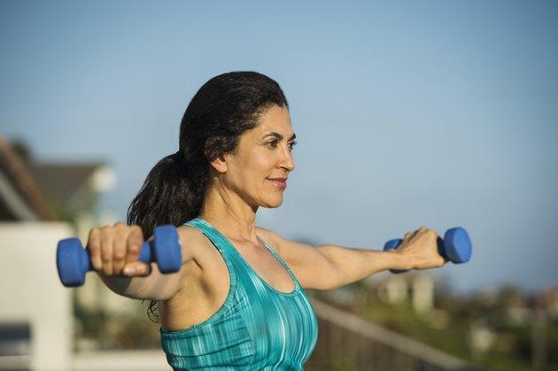 Hispanic woman lifting weights outdoors