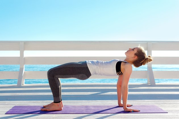 Woman practicing yoga in table pose outdoors at white wooden seafront