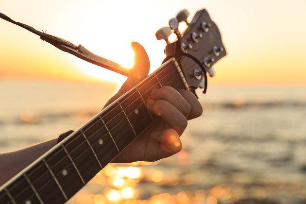 Young guy playing a guitar at sunset