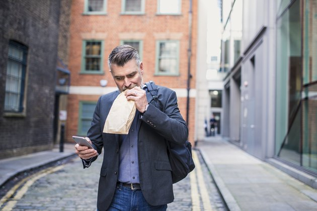 Businessman eating a sandwich and using smart phone
