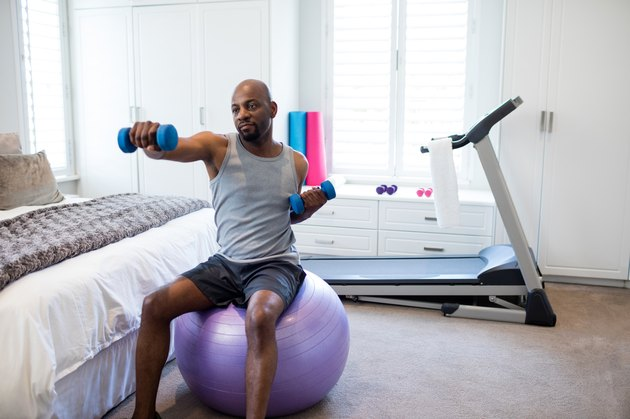 Man exercising with dumbbells on fitness ball in bedroom