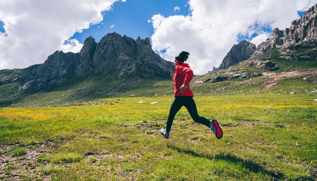 Woman ultra marathon trail runner running on beautiful mountains