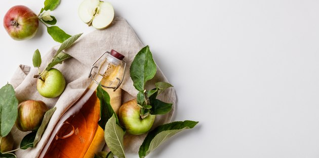 Close-Up Of Apple Cider Vinegar In Bottle Against White Background