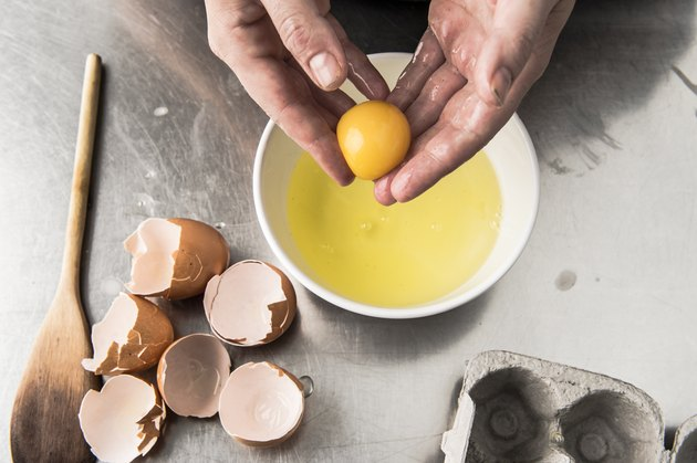 Hands holding egg yolk