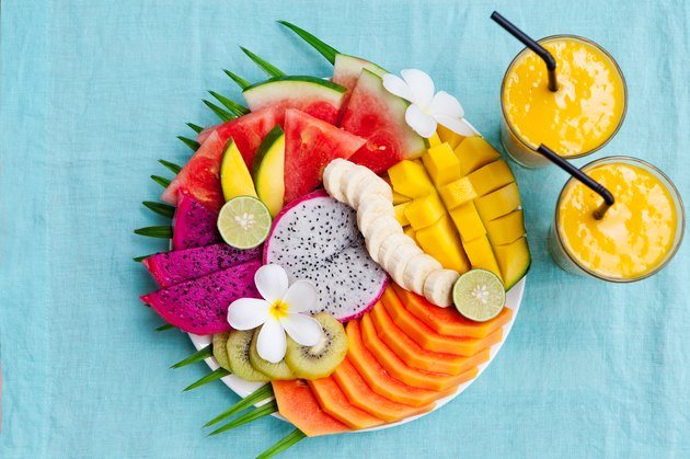 Assortment of fruits that contain serotonin on a white plate with palm tree leaf with mango smoothie, textile blue background. Top view. Copy space