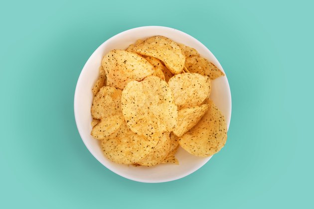 Close-up of potato chips in a bowl on turquoise background to avoid before colonoscopy procedure
