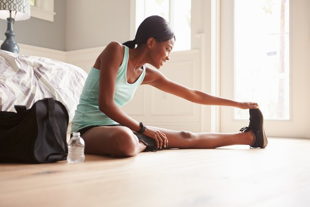 Young black woman sitting on the floor at home stretching