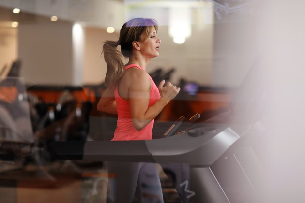 A fit woman running on a treadmill at a fitness center