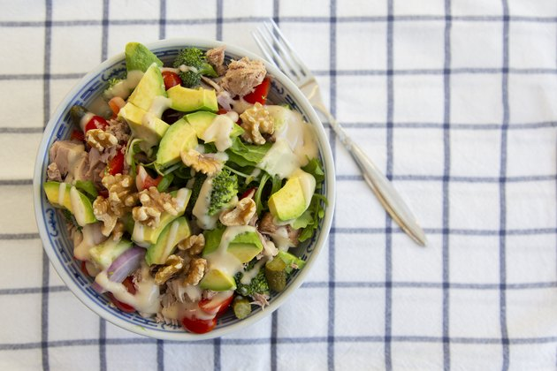 Tuna and avocado salad with walnuts on striped tablecloth for a keto diet