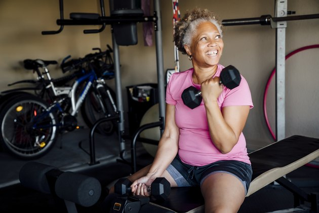 A 50-year-old woman losing weight by lifting weights in her garage