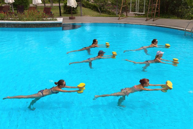 people doing exercise with aqua dumbbell in a swimming pool