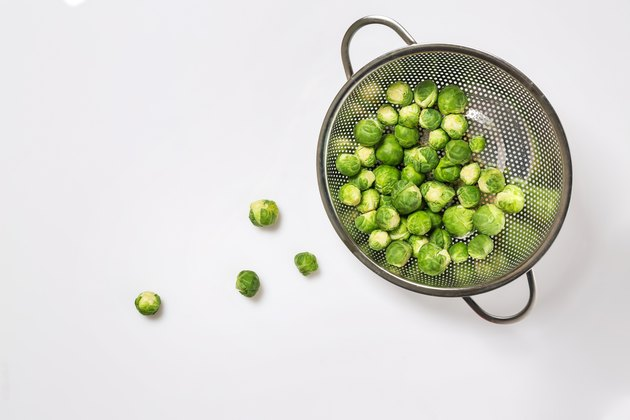 Colander with Brussels cabbage on white background