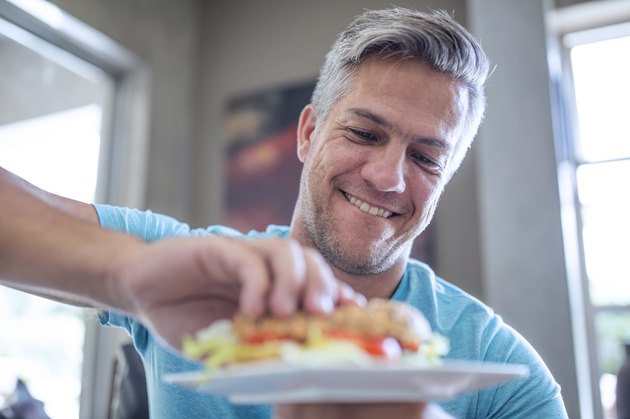 A man eating a sandwich for lunch at home