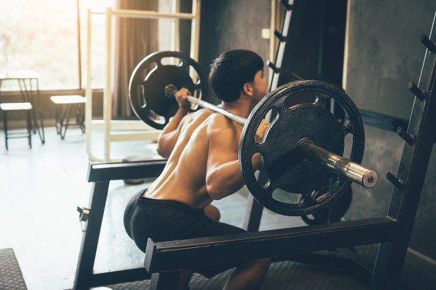 Athletic man performing barbell back squats at the gym.