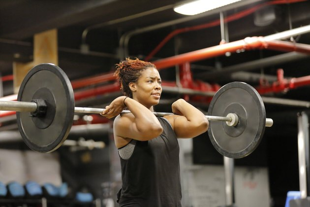 Fit, young African American woman working out with barbells in a fitness gym.