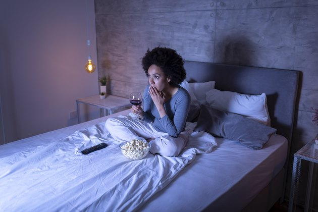 A woman watching a movie on her bed while eating popcorn and drinking a glass of wine