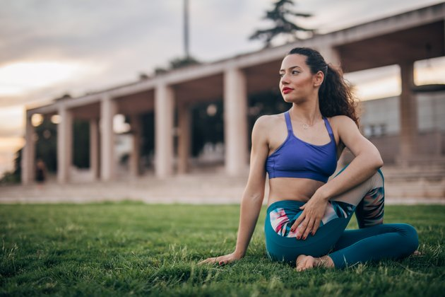 Woman doing yoga in the park, stretching for hip mobility