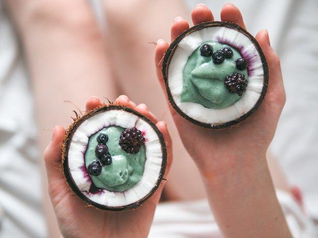 Two coconut half spirulina smoothie in woman hands