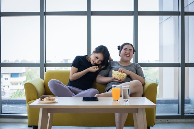 Overweight woman and asian girl enjoy eating food on sofa at home
