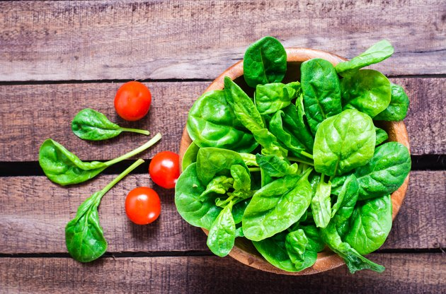 Fresh baby spinach leaves in a bowl and cherry tomatoes on a wooden table