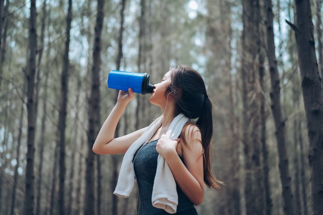 Beautiful asian woman drinking protein shake in the forest nature autumn for relaxing recovery healthy lifestyle with listening music with earphone sport outdoor.