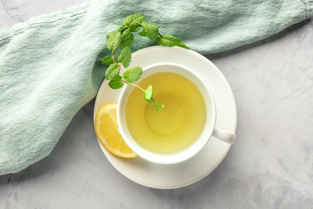 A cup of green tea with lemon and mint leaves.