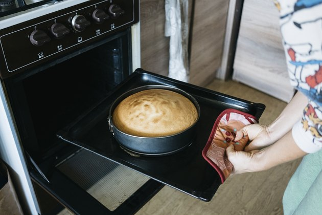 Midsection of woman preparing cake in oven at home