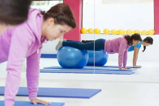 healthy women doing crunches with a yoga ball.