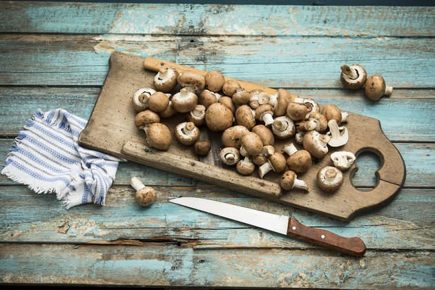Crimini mushrooms on wooden chopping board