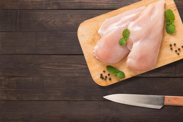 Top view raw chicken on cutting board on wooden.