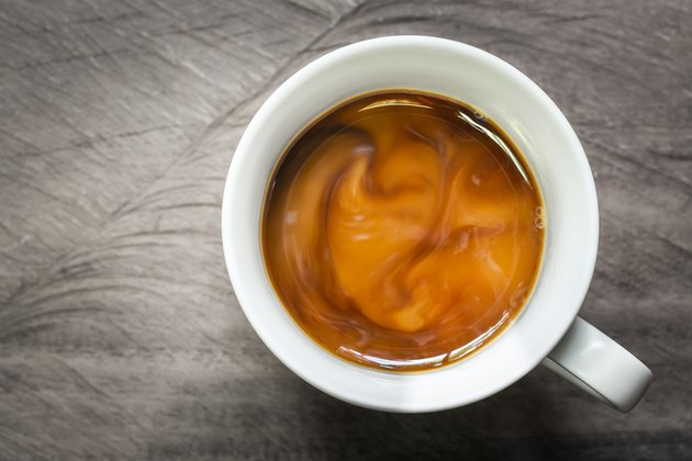 Cup of coffee with flowing milk on wooden background, overhead shot.