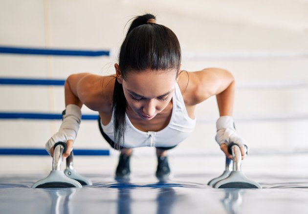 Young fit woman doing planks in gym