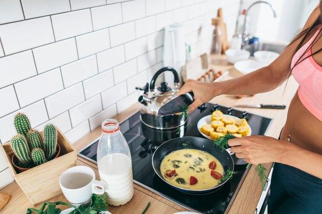 Fit woman preparing healthy breakfast in kitchen