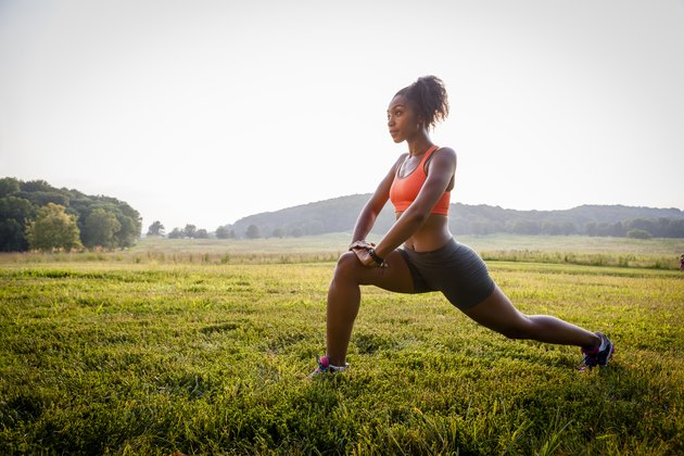 Young female runner stretching in rural park