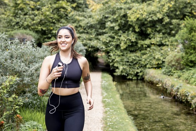Young female runner listening to earphones while running on riverside path