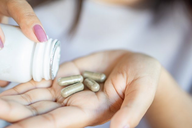 woman hand taking herb medicine tablets