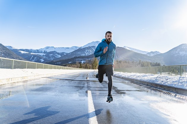 man running on a road in winter with exposed skin