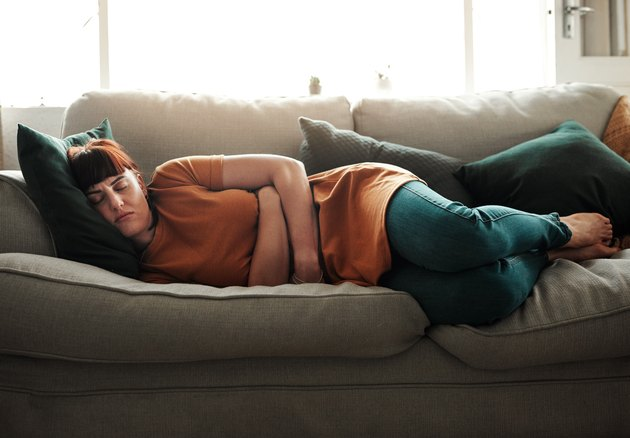 Woman feeling sick on the couch.