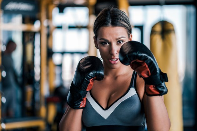 Close-up of a young fit woman in boxing gloves, front view.