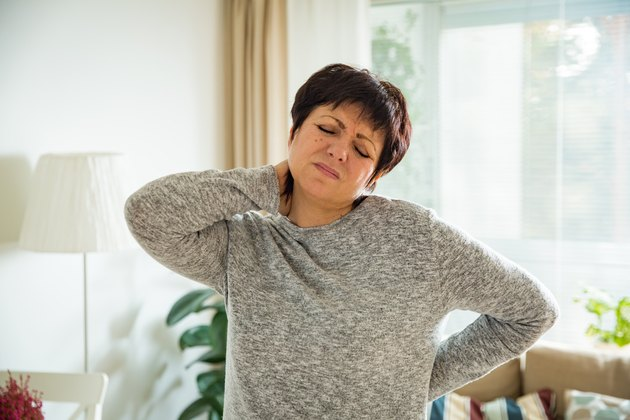 Mature woman suffering from an achy spine and headaches