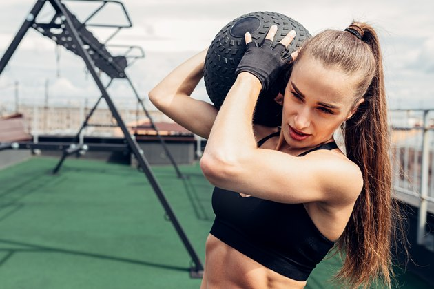 Muscular woman lifting medicine ball while exercising on rooftop