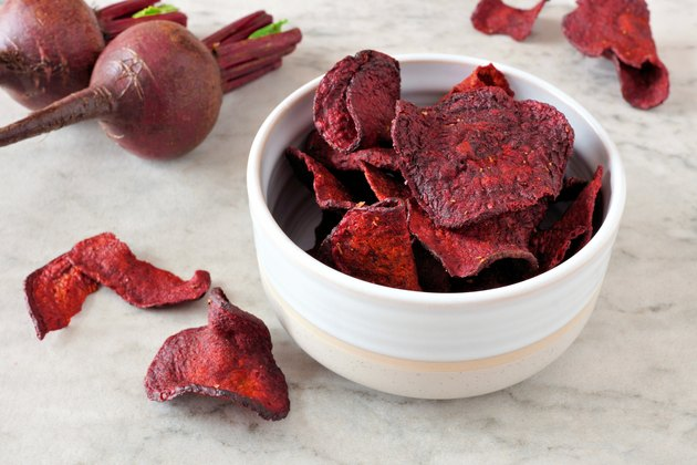Bowl of healthy beet chips over white marble