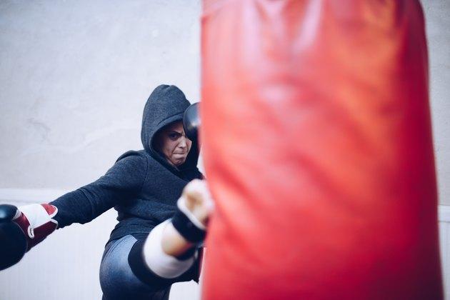 Young female kickboxer kicking punching bag at gym