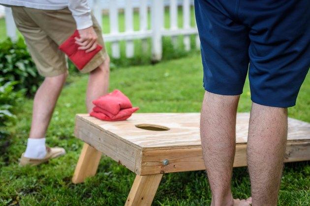 Young men playing cornhole game in backyard