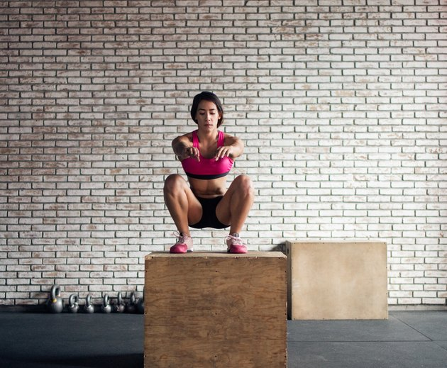 Concentrated woman squatting over a plyo box